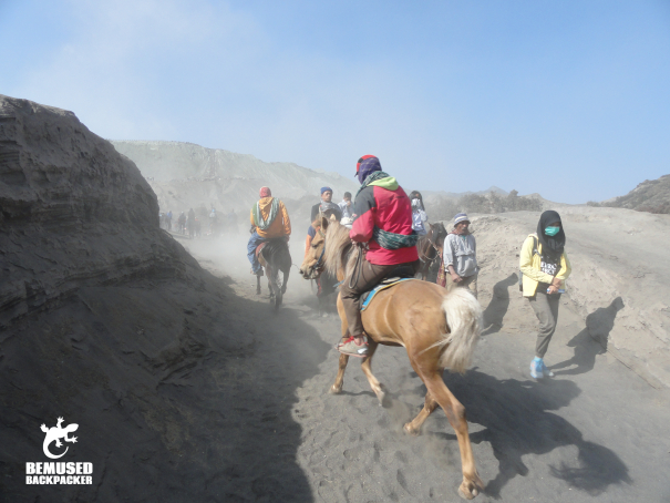 Tourists riding horses on the sea of sand Mount Bromo Indonesia
