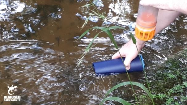 Refilling GRAYL water bottle in a stream